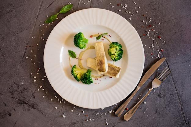 Köstlicher weißer fisch diente auf der weißen platte auf dem grauen hintergrund. restaurant.