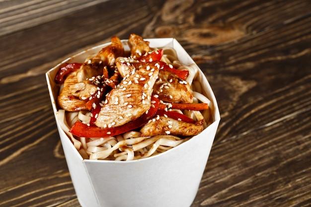 Köstlicher woknudelkastenbehälter mit udon und huhn auf holztisch. chinesisches und asiatisches fast food zum mitnehmen. Premium Fotos