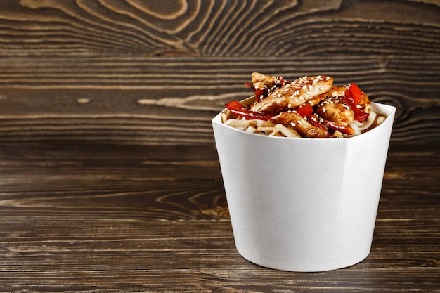 Köstlicher woknudelkastenbehälter mit udon und huhn auf holztisch. chinesisches und asiatisches fast food zum mitnehmen.