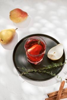 Köstlicher würziger heißer glührotwein mit zimt, sternanis und birnenscheibe serviert in karaffe und glas für einen kalten winterabend oder ein festliches weihnachtsgetränk