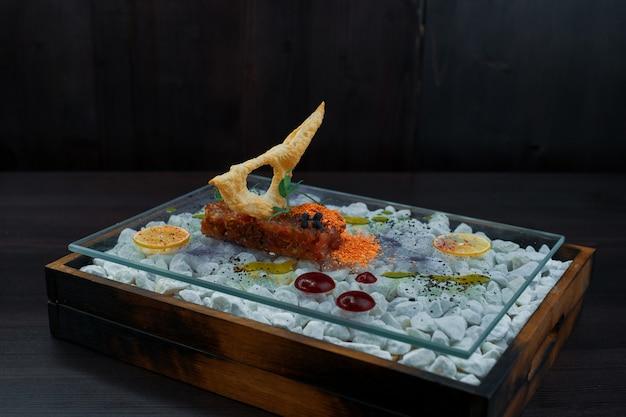 Köstlicher zahnstein des roten fisches mit einem cracker mit einer soße auf einem schönen glasbrett steht auf einem tisch in einem café. gesundes essen aus rohem fleisch. nahansicht