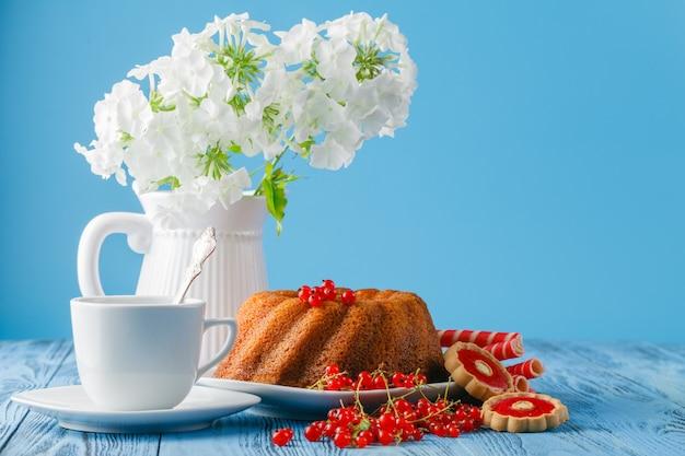 Köstlicher zitronenkuchen auf blauem hintergrund mit beeren und blumen