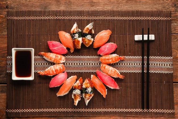 Köstliches, appetitliches set aus buntem nigiri-sushi, serviert als kreis auf brauner strohmatte, flach. japanische traditionelle meeresfrüchte.