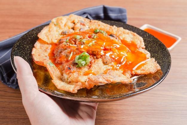 Köstliches austernoberteil des thailändischen lebensmittels briet im eiteig (hoi tod thai language) auf einer platte, die das populäre lebensmittel in thailand ist