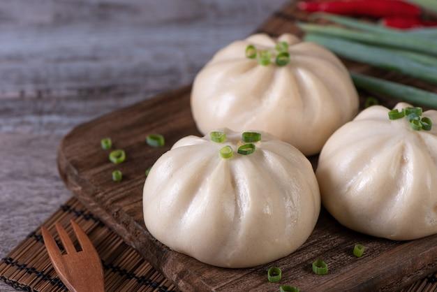 Köstliches baozi chinesisches gedämpftes fleischbrötchen ist bereit, auf servierteller und dampfgarer-nahaufnahmekopierraum-produktdesignkonzept zu essen