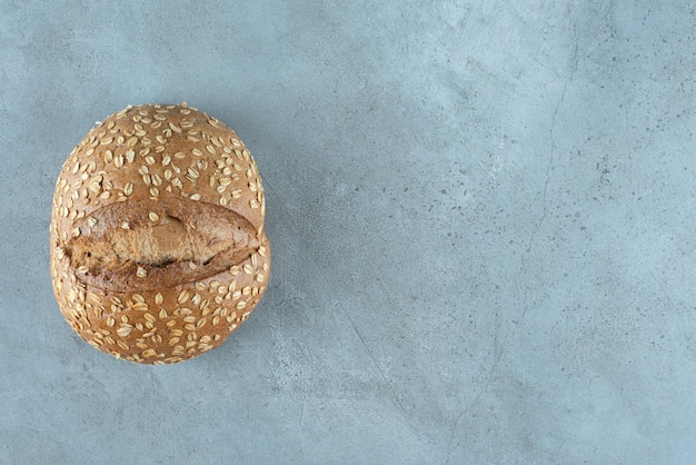 Köstliches brötchen mit samen auf marmor.