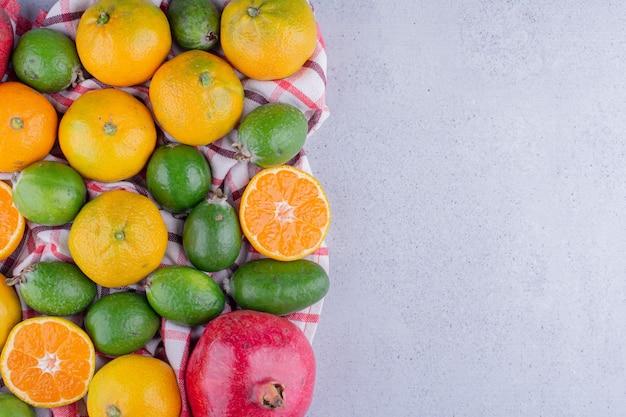 Köstliches bündel mandarinen, feijoas und granatäpfel auf marmorhintergrund. foto in hoher qualität
