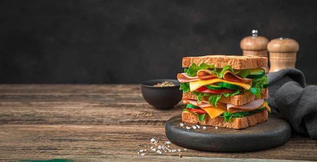 Köstliches club-sandwich mit gemüse-schinken-käse und gebratenem toast auf braunem hintergrund