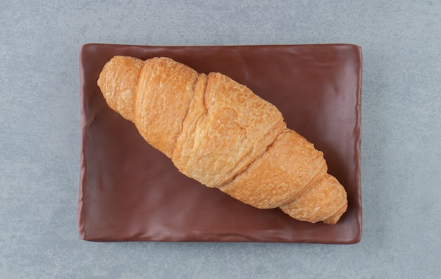 Köstliches croissant auf teller, auf dem marmorhintergrund. hochwertiges foto