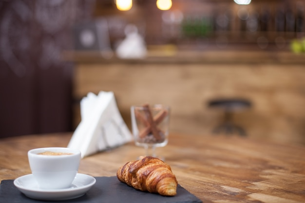 Köstliches croissant serviert mit einer warmen tasse kaffee. vintage-café. frisch gebacken.