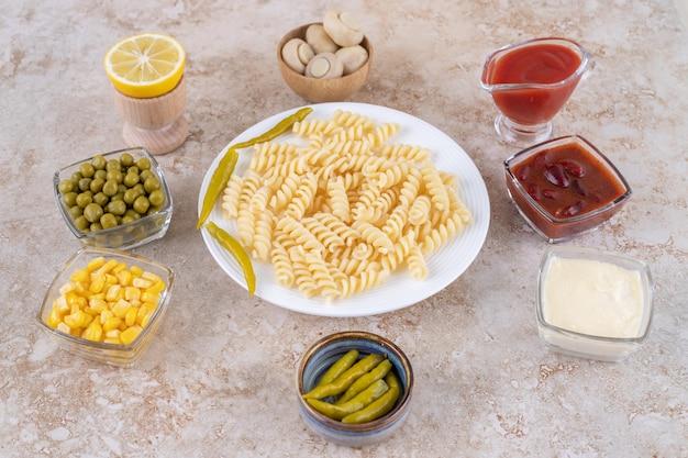 Köstliches dinner-set mit hauptgericht, umgeben von dressings und vorspeisen auf marmoroberfläche.
