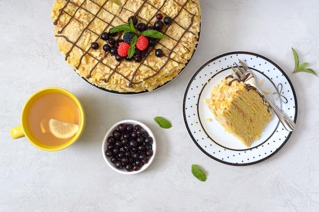 Köstliches festliches schichtdessert mit blätterteig und pudding, dekoriert mit frischen beeren und einer tasse zitronentee
