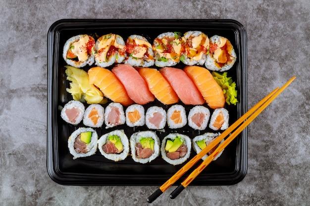 Köstliches frisches sushi-rollen-set auf einem schwarzen tablett. japanisches essen. draufsicht.
