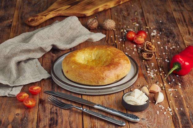 Köstliches frisches tandoorbrot auf holztisch. nationales kaukasisches essen, essen, brot.