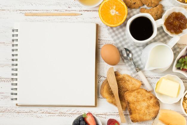 Köstliches frühstück der draufsicht mit notizbuch