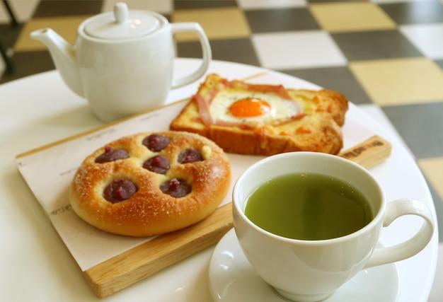 Köstliches frühstück des heißen grünen tees mit gebackenem toast und brötchen