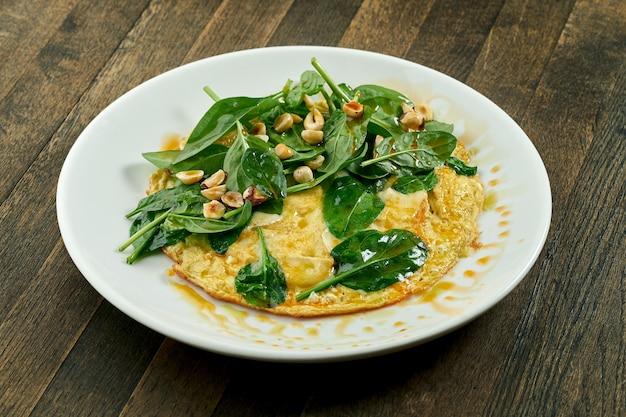 Köstliches frühstück - französisches rührei mit spinat, brie, haselnüssen und würzigem olivenöl in einem weißen teller auf einer holzoberfläche. nahaufnahme, selektiver fokus