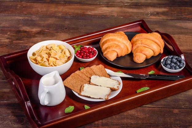 Köstliches frühstück mit frischen hörnchen und reifen beeren auf einem schönen holztisch