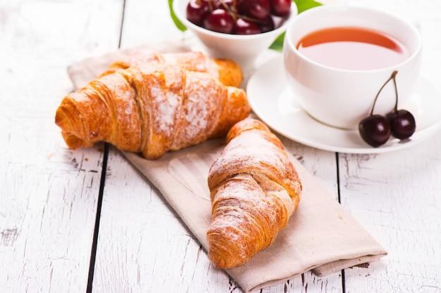 Köstliches frühstück mit frischen hörnchen und reifen kirschen auf weißem hölzernem hintergrund