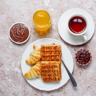 Köstliches frühstück mit kaffee, orangensaft, waffeln, hörnchen, stau, nusspaste auf heller, draufsicht