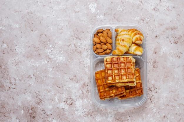 Köstliches frühstück mit mandeln, scheiben der roten äpfel, waffeln, hörnchen auf plastikbrotdose auf licht