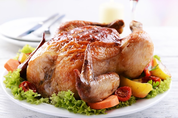 Köstliches gebackenes huhn auf teller auf dem tisch auf hellem hintergrund