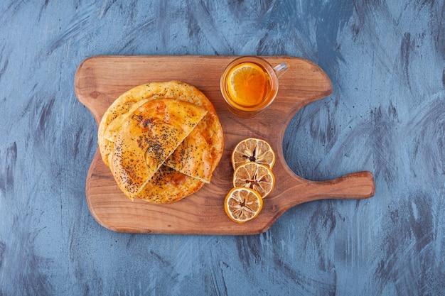 Köstliches gebäck gefüllt mit käse und einer tasse tee auf holzschneidebrett.