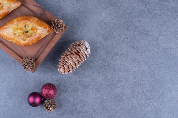 Köstliches gebäck mit weihnachtskugeln auf einem holzbrett