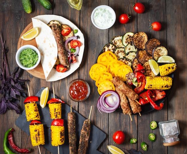 Köstliches gegrilltes gemüse und döner kebab auf einem hölzernen hintergrund