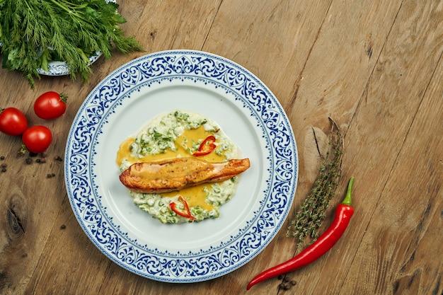 Köstliches gegrilltes lachssteakfilet mit erbsen in einer cremigen sauce in einem weißen teller auf einer holzoberfläche. leckere meeresfrüchte