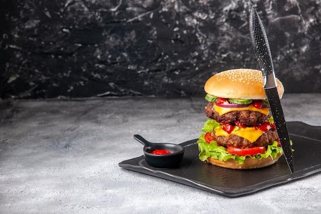Köstliches hausgemachtes sandwich und gabel auf schwarzem tablett auf der linken seite auf grauer, beunruhigter, isolierter oberfläche