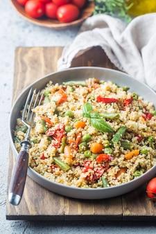 Köstliches hausgemachtes vegetarisches cous cous mit tomaten, karotten, grünen bohnen, paprika und frischem basilikum