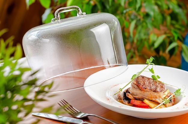 Köstliches kalbsmedaillon mit gemüse und mikrogrün auf weißem teller mit glaskappe. restaurant menü konzept