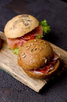 Köstliches knuspriges burgerbrötchen mit geschnittenem schinken auf einem vintage-holzschneidebrett. dunkles launisches essen stillleben.