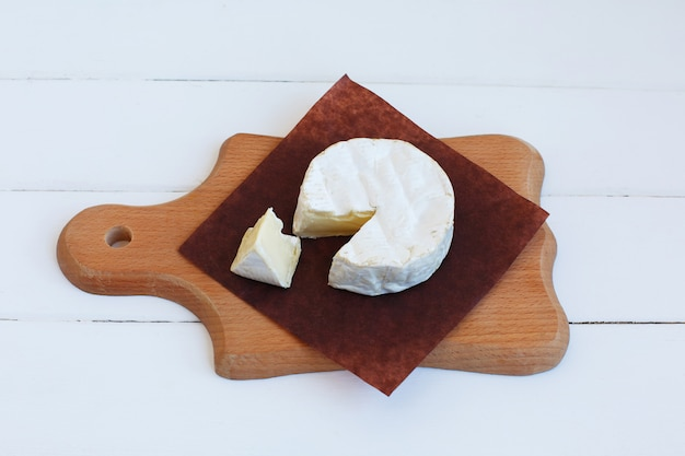 Köstliches lebensmittel des französischen feinschmeckerischen runden milchprodukts der traditionellen normandie des camembertkäses auf rustikalem pergament.
