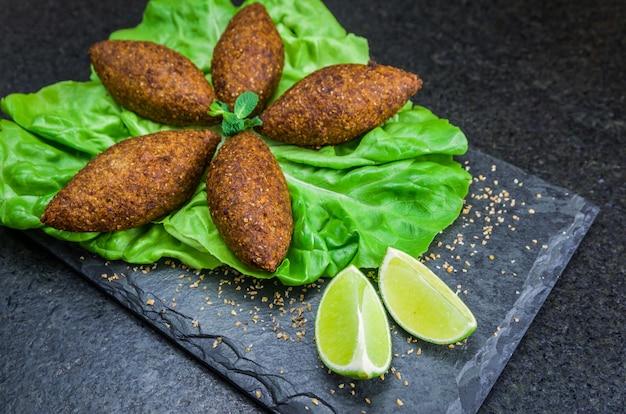 Köstliches libanesisches essen, kibbeh (kibe) auf schwarzem schieferstein und granithintergrund.