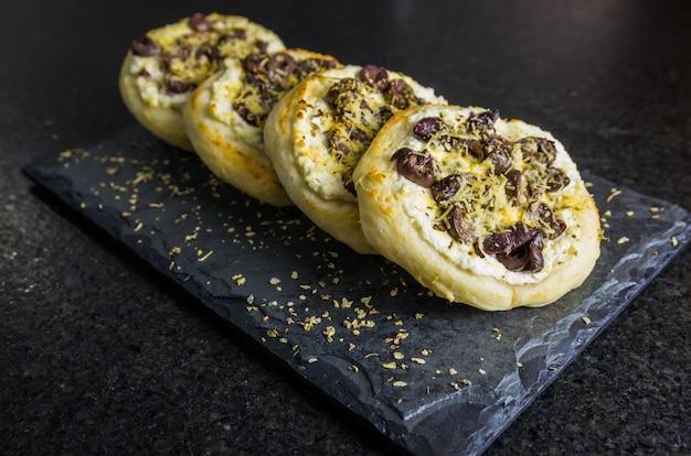 Köstliches libanesisches essen, mediterrane ricotta-sfiha, gratinierte oliven mit käse auf schwarzem granithintergrund.