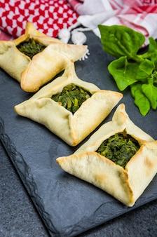 Köstliches libanesisches essen, spinat-sfiha auf schwarzem schiefersteinhintergrund und traditioneller libanesischer turban keffiyeh.