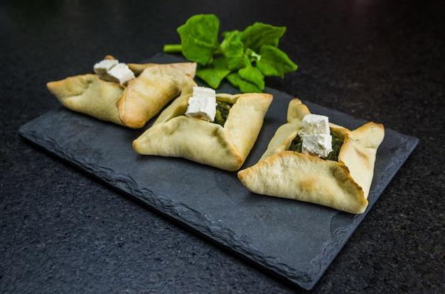 Köstliches libanesisches essen, spinat-sfiha mit ricotta-käse auf schwarzem steinhintergrund.