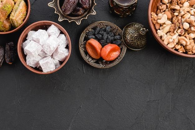 Köstliches lukum; trockenfrüchte und nüsse auf schwarzem strukturiertem hintergrund