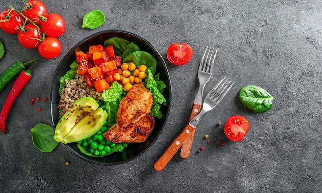 Köstliches mittagessen mit quinoa, avocado, schwitzkartoffel, brathähnchen und gewürzen auf dunklem hintergrund. ansicht von oben.