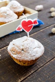 Köstliches muffin mit puderzucker und einer herzförmigen kerze auf einem holztisch. festliche kuchen. alles gute zum geburtstag.