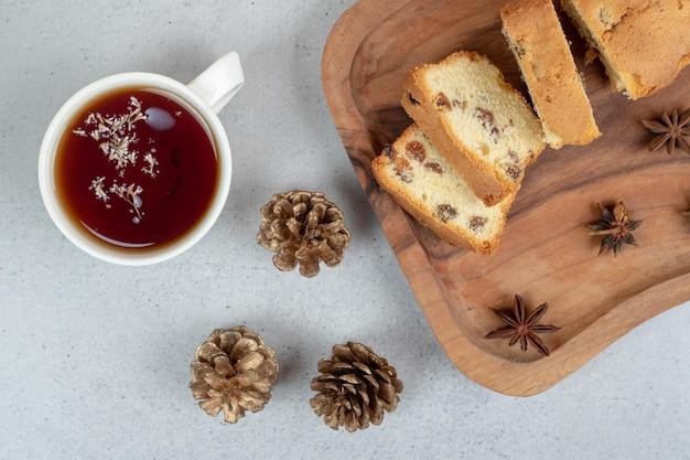 Köstliches muffin mit rosine und tasse tee auf holzbrett.