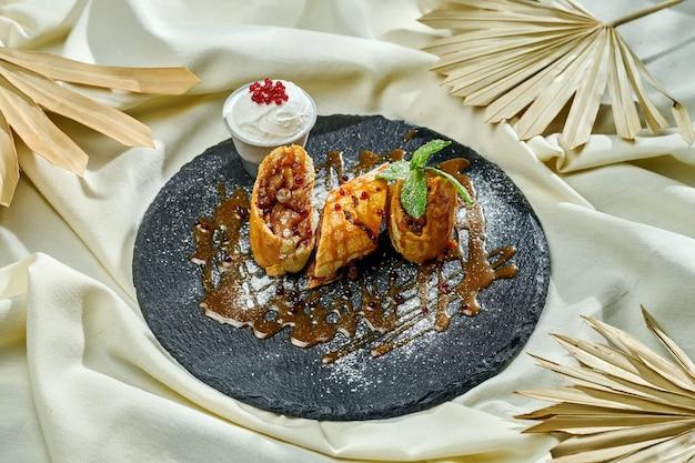 Köstliches österreichisches dessert - apfelstrudel mit eis auf einer tischdecke. gebäck