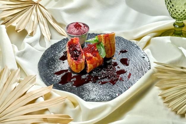 Köstliches österreichisches dessert - kirschstrudel mit eis auf einer tischdecke. gebäck