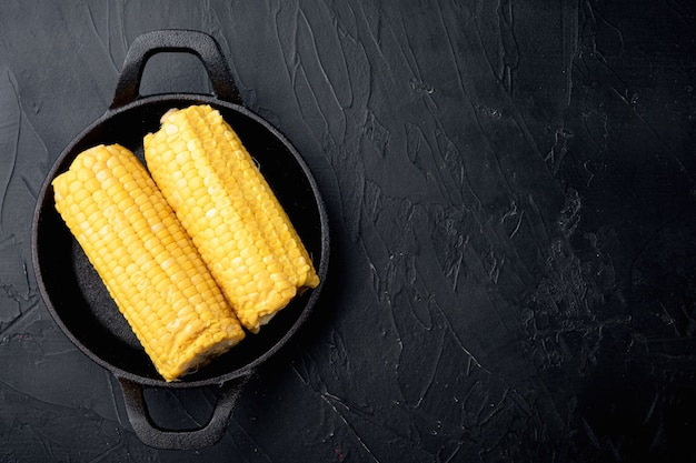 Köstliches saftiges süßes gekochtes maisset, auf schwarzem steintisch, draufsicht flach liegend