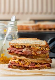 Köstliches sandwich mit fleisch, gebratenen zwiebeln, käse und senf auf dem grill, abendessen der männer