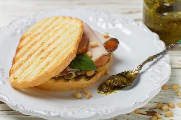 Köstliches sandwich mit gebackenem schinken, käse, pesto-sauce und pinienkernen