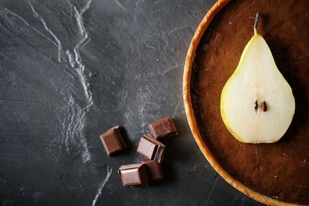 Köstliches schokoladenbirnentörtchen auf schiefer mit textraum