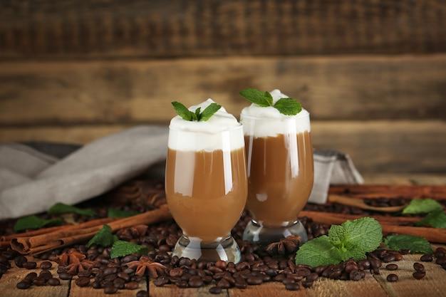 Köstliches schokoladenmilchdessert mit kaffeebohnen und minze auf holzoberfläche